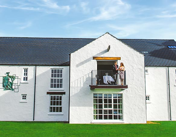 A couple on the balcony of the Mast Distiller's Suite at The Bushmills Inn